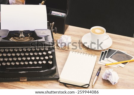 empty ruled notebook with frame of black vintage typewriter and coffee on table, retro toned - stock photo