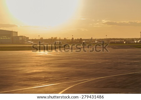 Empty runway at the airport in anticipation of landing the plane. Sunset. Concept travel. - stock photo