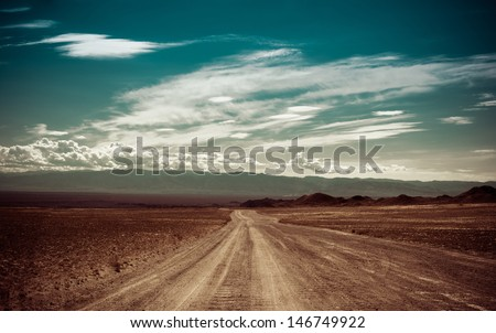 Empty rural road going through prairie under cloudy sky in Charyn canyon. State National Paleontology Park in Kazakhstan. Vintage style processing image - stock photo