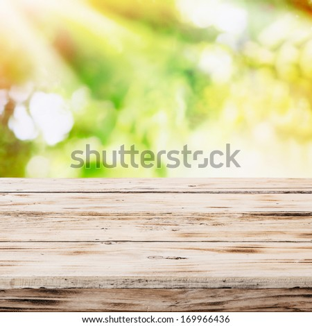 Empty rustic wooden table with golden rays of sunlight in a sunburst pattern over a blurred green country garden and bokeh suitable for product placement depicting a healthy lifestyle - stock photo