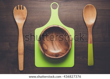 empty salad bowl and two spoons on wooden table - stock photo
