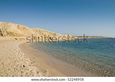 Empty sandy beach in a tropical lagoon with turquoise water and a clear blue sky. Ras Mohamed National Park, South Sinai, Red Sea, Egypt.