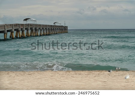 Empty, sandy beach on stormy day with a long pier jutting out into the ocean.  The sky is overcast and cloudy which adds to the feeling of loneliness conveyed by the empty pier and empty beach. - stock photo