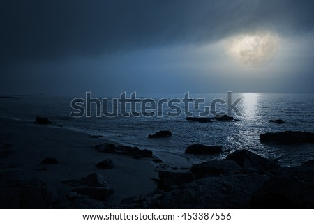 Empty seaside with rocks in a full moon night - stock photo