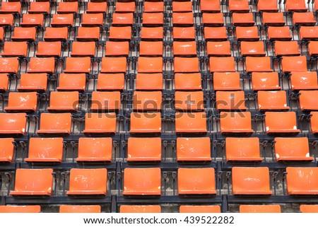 empty seats orange plastic in a stadium. - stock photo