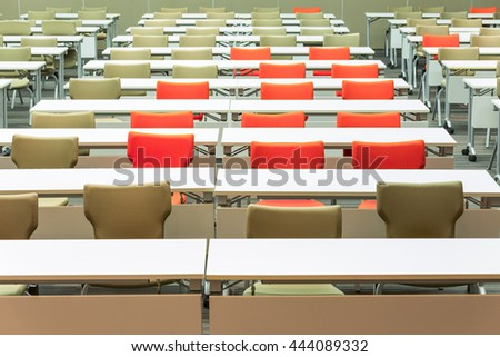 Empty seats with tables in a conference hall. - stock photo