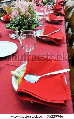 Empty served restaurant table with red tablecloth