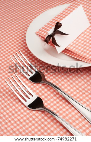 Empty served restaurant table with tablecloth, napkin and guest card - stock photo