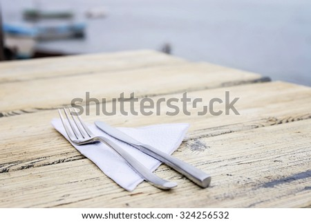 Empty Set In Restaurant. Fork, Knife and Napkin on White Wooden Table. - stock photo