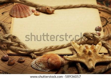 Empty sheet of exercise book, seashells, rope, lying on the maps - stock photo