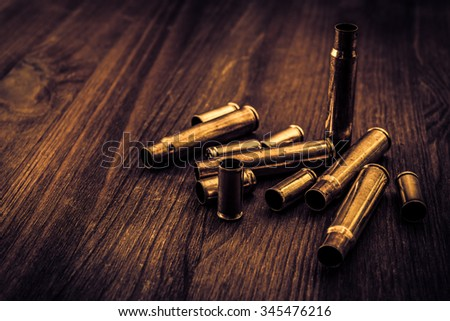 Empty shells from the weapons lying on a wooden table. Image vignetting and the yellow-blue toning - stock photo