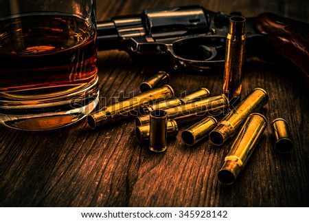 Empty shells from the weapons with glass of whiskey and revolver on a wooden table. Image vignetting and the orange-blue toning - stock photo