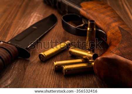 Empty shells with rifle and combat knife lying on a wooden table. Close up view, focus on the shells - stock photo