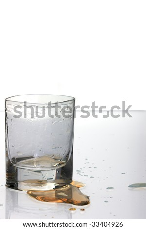 Empty shot glass with spilled drink on the table. - stock photo
