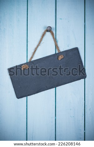 empty signboard with rope hanging on planks background - stock photo