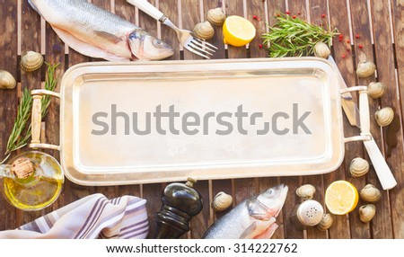 Empty silver tray with frame of seabass fish, shellfish and spices - stock photo