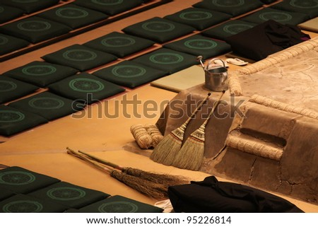 Empty sitting pillows and brooms as equipment next to a fighting ring in a sumo arena in Tokyo, Japan - stock photo
