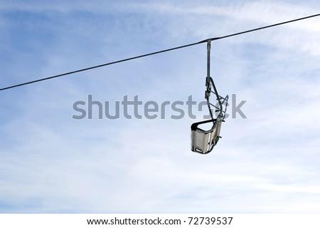 Empty ski lift chair on bright winter day. - stock photo