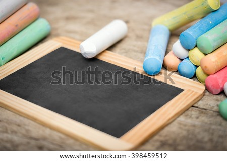 empty Slate with copyspace and colorful crayon on wooden table - stock photo