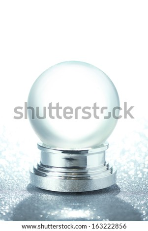 Empty snow globe on glittering background