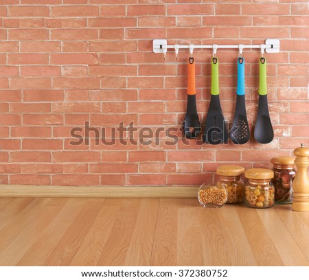 Empty space on the kitchen counter with utensils on hooks against brick wall - stock photo