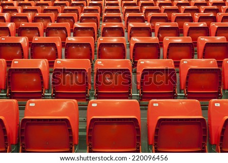 Empty stadium red seats before a match - stock photo