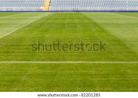 Empty stadium with chairs on a platform and fresh green - stock photo