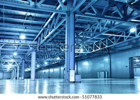 Empty storehouse toned in the blue color - stock photo