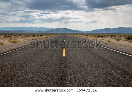 Empty straight highway in the West - stock photo