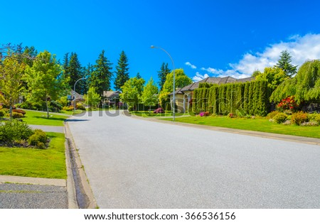 Empty street at the nice and comfortable great neighborhood, community. Some homes on the empty street in the suburbs of Vancouver, Canada. - stock photo