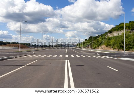 Empty street in empty town. Blue sky and white cloud - stock photo