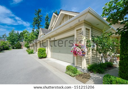 Empty street of the nice neighborhood with the houses with double doors garages and hanging buckets with flowers in the suburbs of Vancouver, Canada. - stock photo