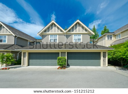Empty street of the nice neighborhood with the houses with double doors garages in the suburbs of Vancouver, Canada. - stock photo