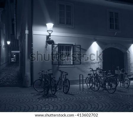 Empty street with bikes near old cafe in city center of Ljubljana at night, Ljubljana, Slovenia - stock photo