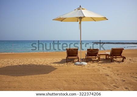 empty sun loungers on the beach - stock photo