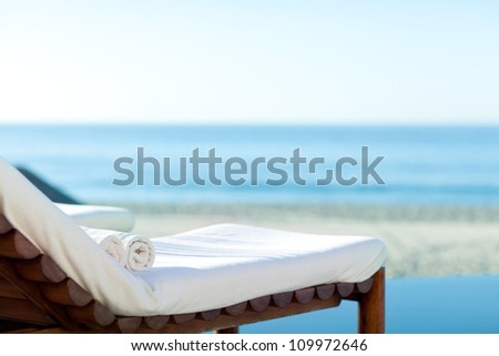 empty sunbed with wrapped towels on a beautiful beach - stock photo