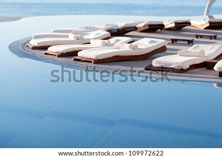 empty sunbeds by the beautiful resort pool - stock photo