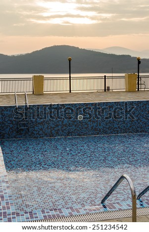 Empty swimming pool with blue tiles in autumn day - stock photo