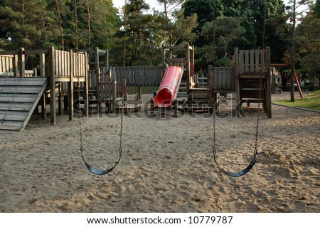 Empty swings in wooden outdoor playground.  Canada. - stock photo
