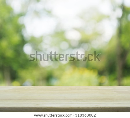 Empty table and blurred green tree bokeh background for your product display montage - stock photo