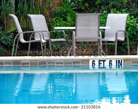 empty table and chairs reflecting in pool