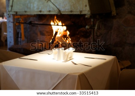Empty table in a restaurant on the background of the fireplace with the fire. - stock photo