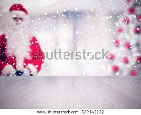 Empty table in front of blurred Santa Claus and Christmas tree. Vintage filter