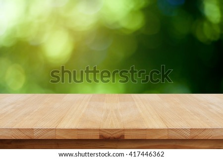 Empty table on blurred green background. - stock photo