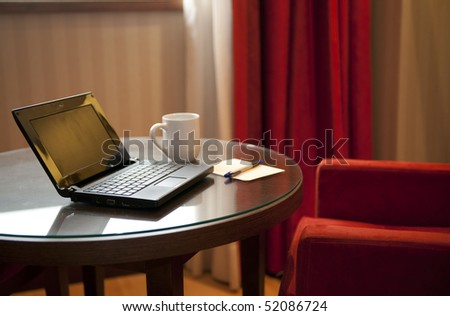 Empty table with laptop and cup - stock photo