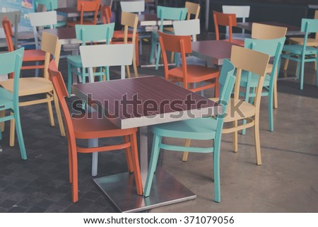 empty tables and chairs in cafe vintage look - stock photo