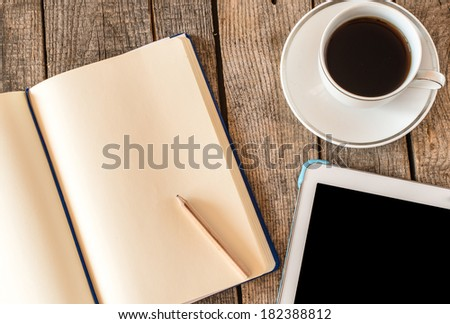 Empty tablet pc and a coffee and notebook with pen on wood table - stock photo