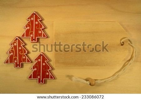 Empty tag with three Christmas decorations on red background. Three Christmas decoration with wooden price tag - stock photo