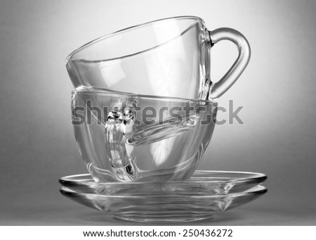 Empty tea saucer cups in spot light on gray background - stock photo