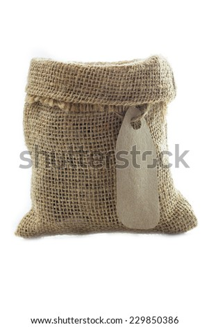 Empty textile burlap sack with blank tag isolated on white background